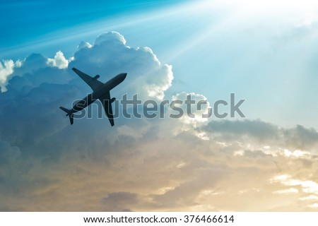 Airplane in the sky and cloud at sunrise - stock photo