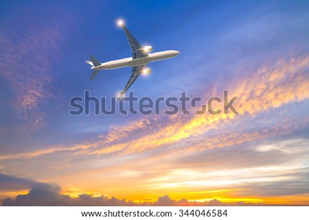 Airplane in the sky at sunrise or sunset. - stock photo