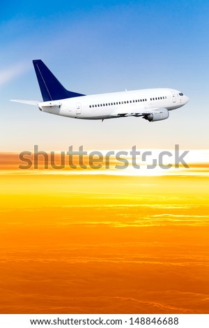 Airplane in the sky at sunset. A passenger plane in the sky - stock photo