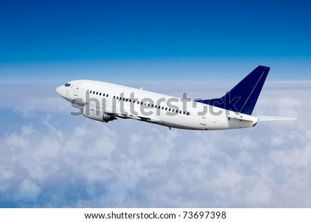 Airplane in the sky, over the cloudy sky - stock photo