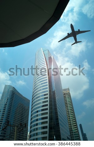 Airplane in the sky with modern buildings