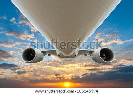 airplane in the sky with sunset - stock photo