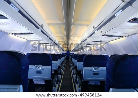 Airplane interior with blue seats and white panel