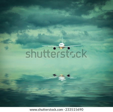airplane into a surreal colorful evening sky with reflection - stock photo