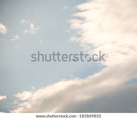 Airplane is flying in the sky among clouds. - stock photo