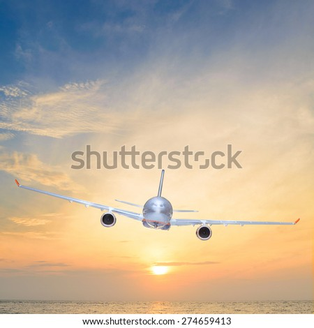 airplane is flying over the sea at sunset