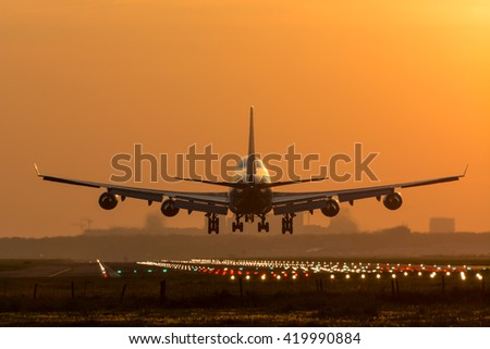 Airplane is flying to the airport, rising sun at the background. - stock photo