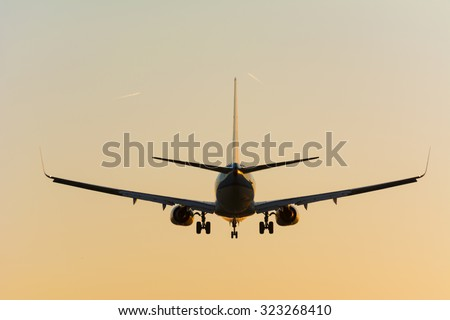 Airplane is flying to the runway. Beautiful colors in the sky during the sunrise.  - stock photo