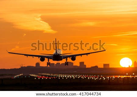 Airplane is flying to the runway during a nice sunrise.