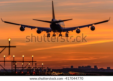 Airplane is flying to the runway during a nice sunrise. - stock photo