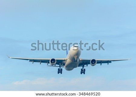 Airplane is flying to the runway from the airport during a cloudy day. - stock photo
