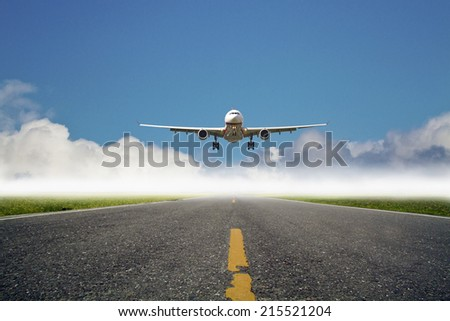 airplane is landing at airport against blue cloudy sky - stock photo
