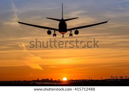 Airplane is landing during a nice early morning sunrise.