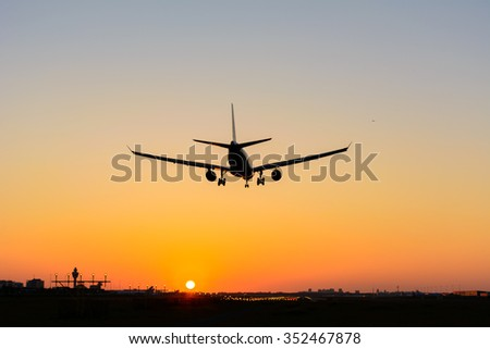 Airplane is landing during a nice sunrise.