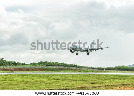 Airplane is landing on the airport before a storm approaching.