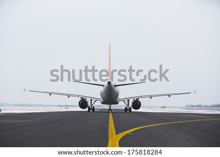 Airplane is taxiing on the airport in winter. - stock photo