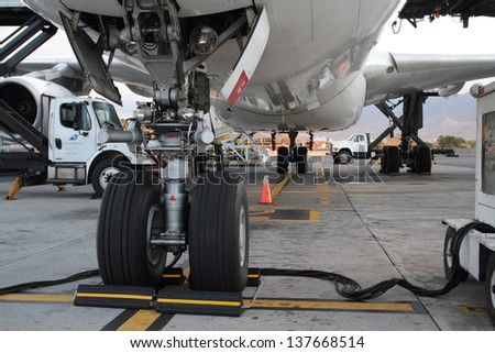 Airplane jetliner being attended on ground - stock photo