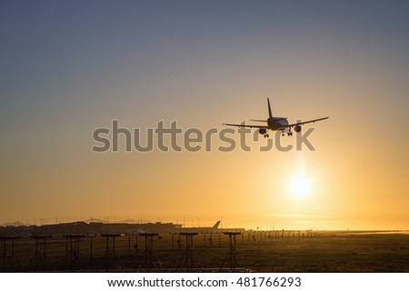 Airplane landing at an airport during a sunny sunset.