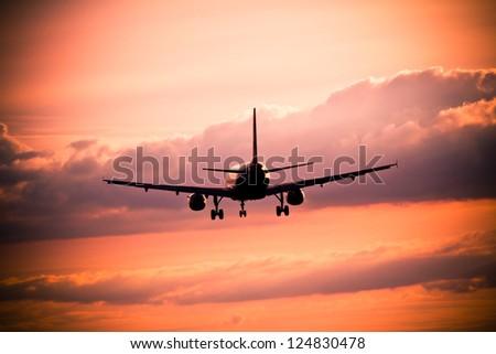 Airplane landing at sunset - stock photo