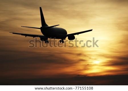Airplane landing at sunset, Prague Ruzyne Airport - stock photo