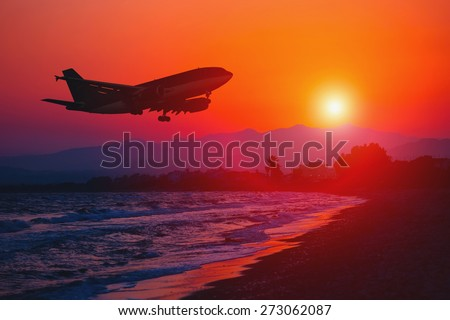 Airplane landing at sunset. Sea and Mountain background. Silhouette of a big aircraft, airline. Transportation. Final approach. Gear down.