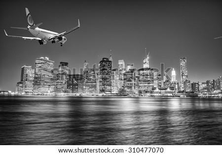 Airplane landing in New York at night. Manhattan skyline on background. - stock photo