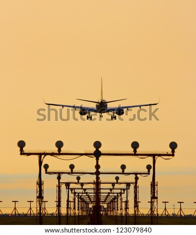 Airplane landing in sunset with landing lights in foreground - stock photo