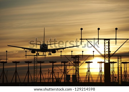 Airplane landing in the sunset - stock photo