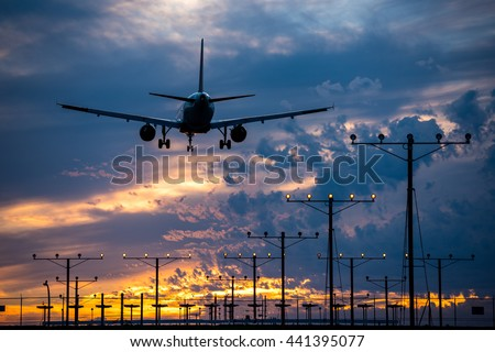 Airplane landing into the sunset