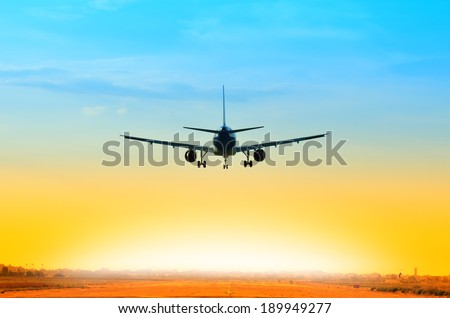 airplane landing on the runway at sunset