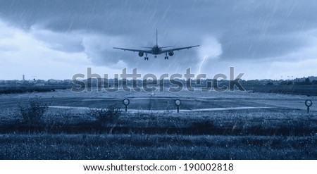 airplane landing on the runway with rain - stock photo