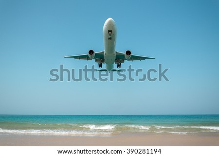 Airplane landing over the sea - stock photo