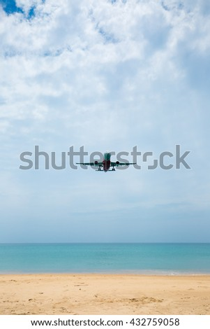 Airplane landing over the sea on cloudy day. - stock photo
