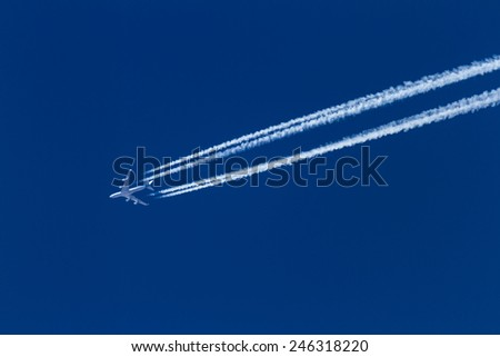 airplane leaving a long trail on a beautiful blue sky - stock photo