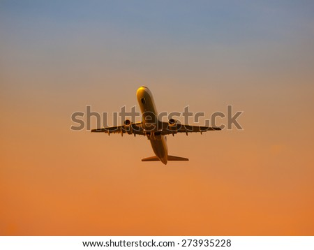 Airplane leaving airport at the sunset, evening departure for holiday - stock photo