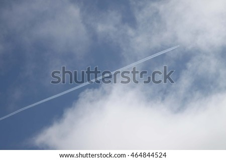 airplane leaving long contrails in blue sky with white clouds