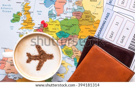 Airplane made of cinnamon in cappuccino, passports, Europe map and no name boarding pass.  Marked point of destination - Germany - stock photo