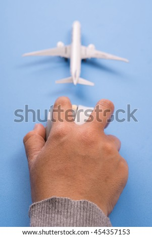 Airplane model and computer mouse on blue background, Online travel booking concept.
