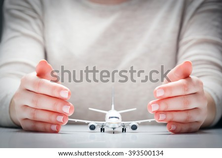 Airplane model surrounded by hands in gesture of protection. Concept of aircraft industry, airline safety, security and insurance. - stock photo
