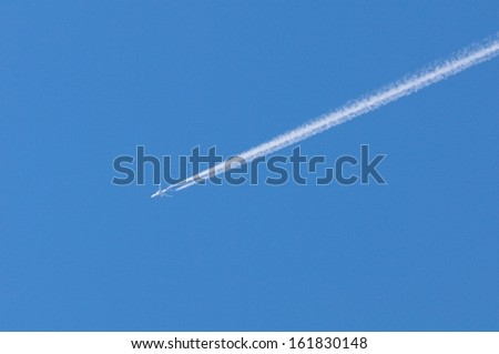 Airplane moving across blue sky with vapor trail - stock photo