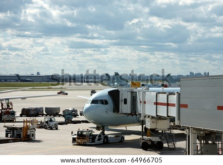 Airplane near the terminal in an airport - stock photo