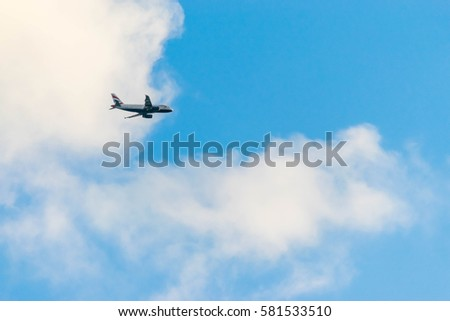 Airplane on a blue sky with clouds.