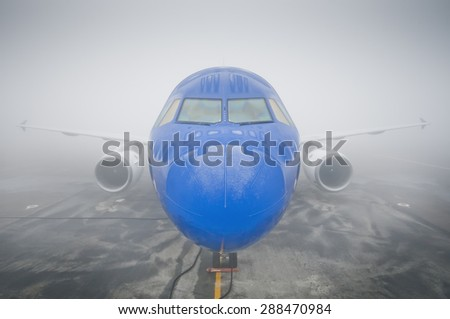 airplane on the runway in fog - stock photo