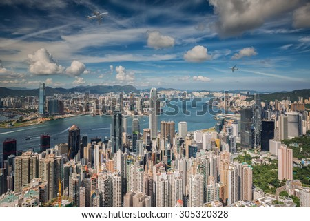 Airplane over Hongkong island with city scape in day time below. - stock photo