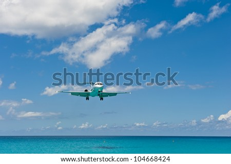 Airplane over water just after taking off. - stock photo