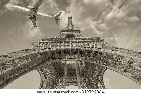 Airplane overflying Eiffel Tower in Paris. - stock photo