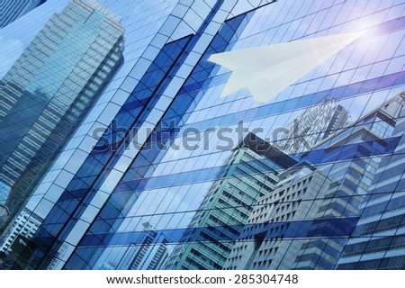 Airplane paper flying on window tower background, leader business concept