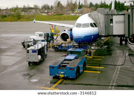 Airplane parked at the gate being loaded with cargo - stock photo