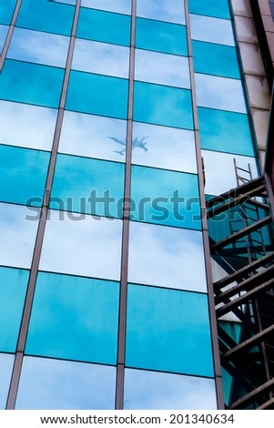 Airplane reflection in the skyscraper mirror facade - stock photo