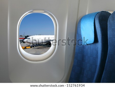Airplane seat and window inside an aircraft - stock photo